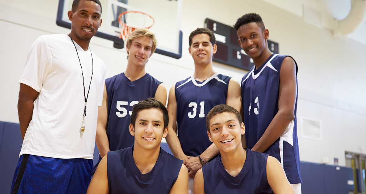 Members Of Male High School Basketball Team With Coach